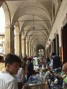 Merchants sell their wares under the arches of the Vasari Loggia in Arezzo.